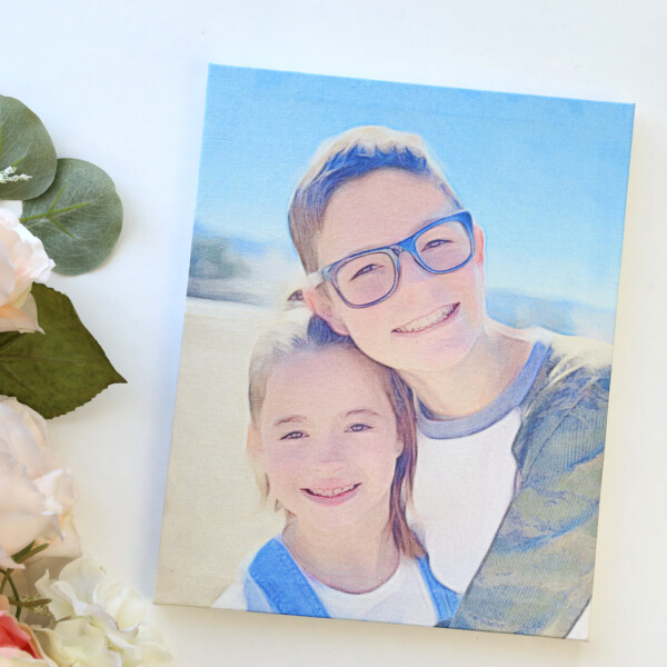 A photo of a boy and girl on a canvas next to flowers