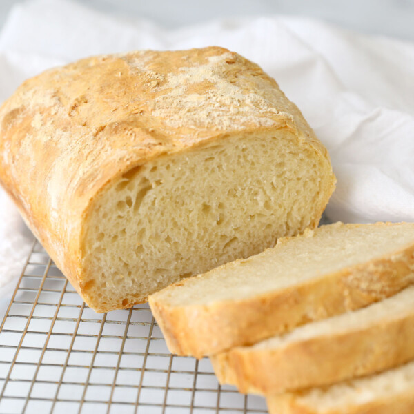 A loaf of 4 ingredient bread, sliced and resting on a cooling rack