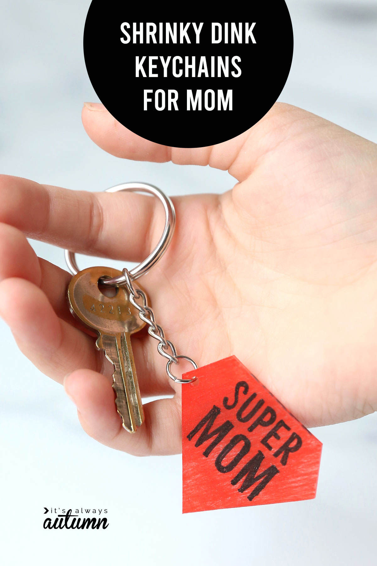 Hand holding key on a super mom keychain and words: shrinky dink keychain for mom