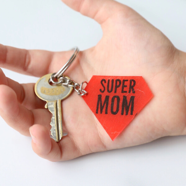 A hand holding a key and Super Mom keychain