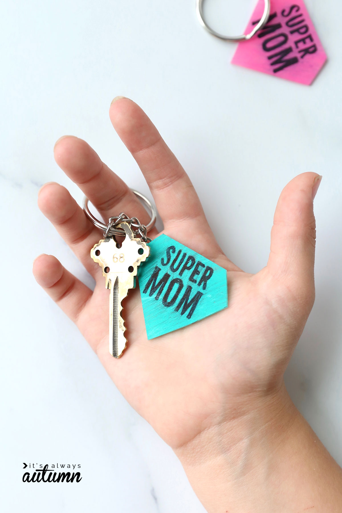 Hand holding a key on a keychain that says supermom