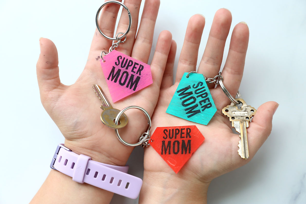 Hands holding DIY shrinky dink keychains that say supermom