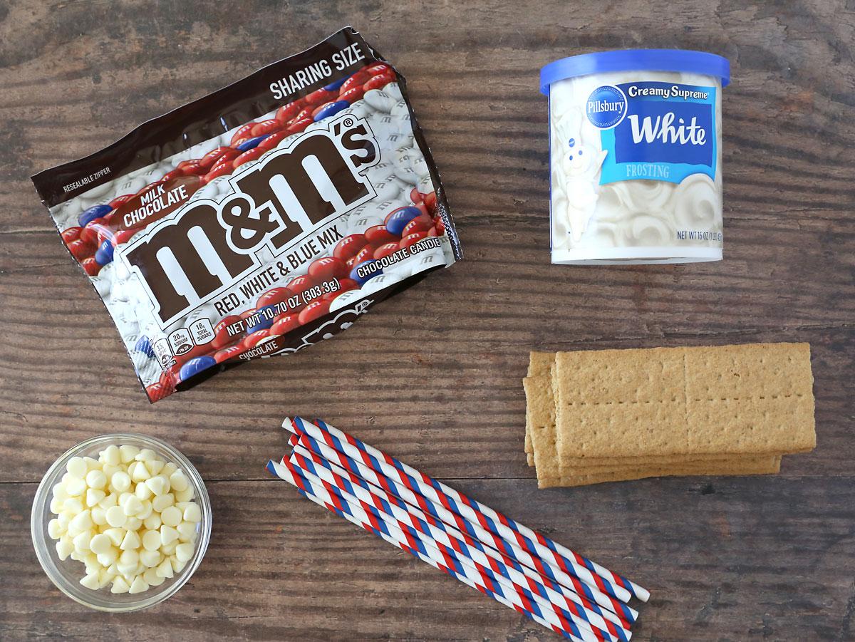Graham cracker flag ingredients: M&Ms, graham crackers, frosting, white chocolate chips, straws