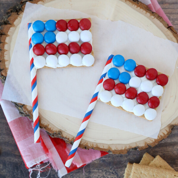 Graham crackers decorated to look like American flags with a paper straw for the flagpole