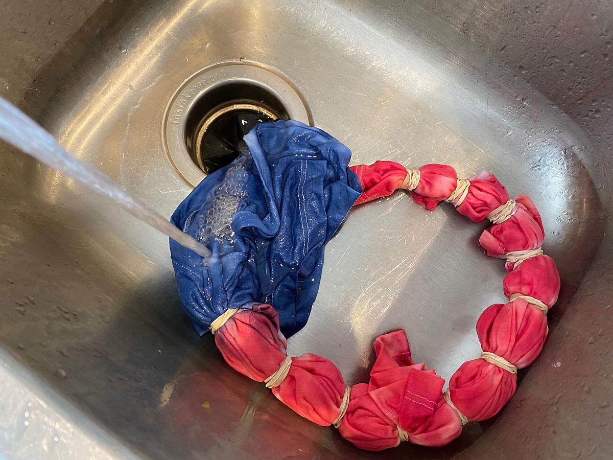 Tie dye shirt getting rinsed in the sink