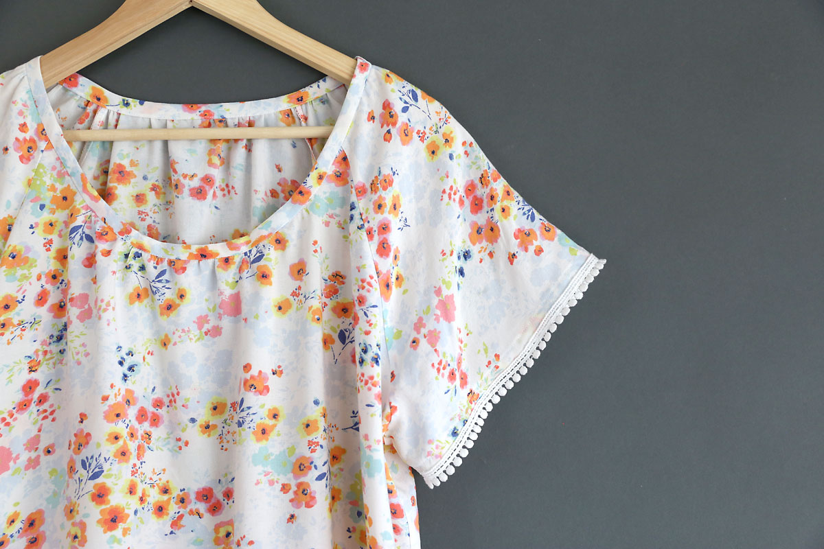 A closeup of a handsewn blouse with pink flowers and white pom pom trim on the sleeve