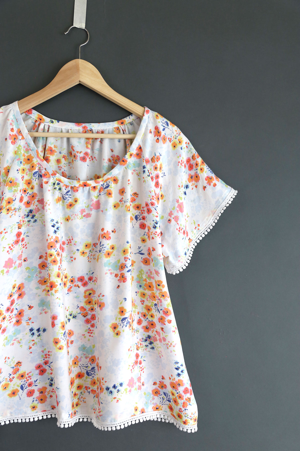 A close up of a handmade blouse with pink flowers and pom pom trim