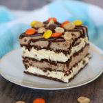 A piece of peanut butter ice cream cake on a plate, with nuts and Reeses pieces on top