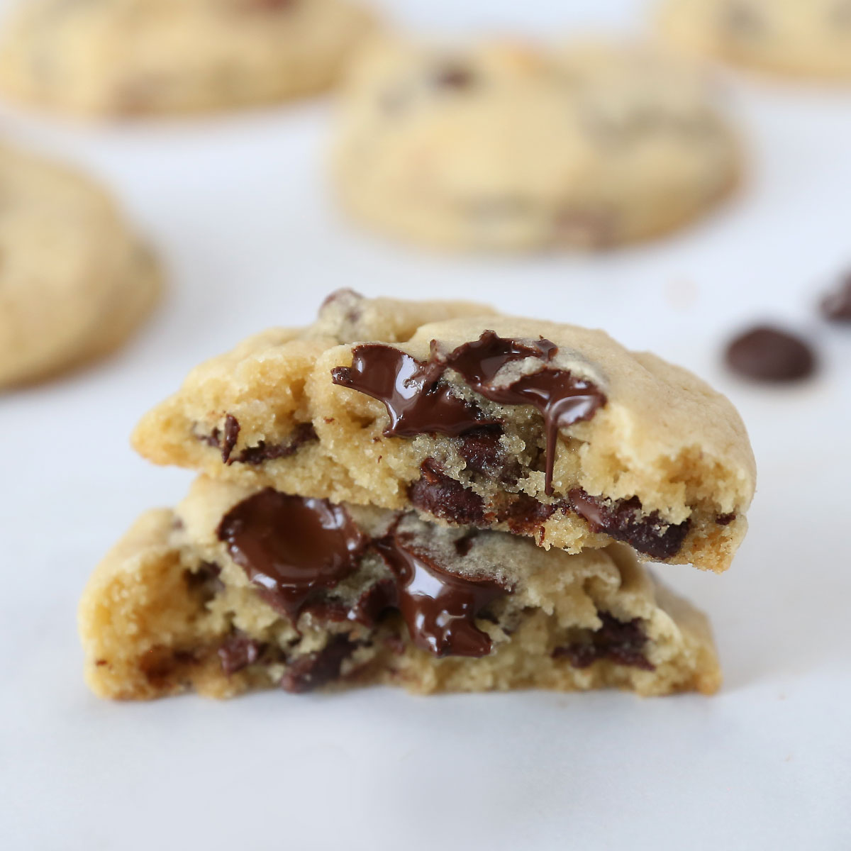A chocolate chip cookie broken in half to show the soft center and melty chocolate