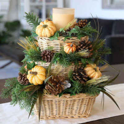 DIY fall centerpiece with baskets, greenery, pinecones, and pumpkins