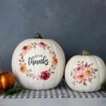 "White craft pumpkins with floral designs and the words ""give thanks"" on them"