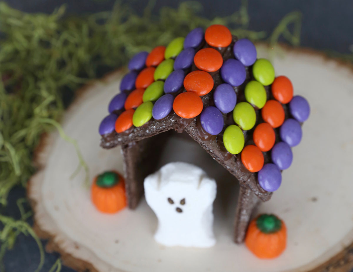 """Halloween """"gingerbread house"""" decorated with Halloween M&Ms, Halloween ghost peep, and pumpkin candy"""