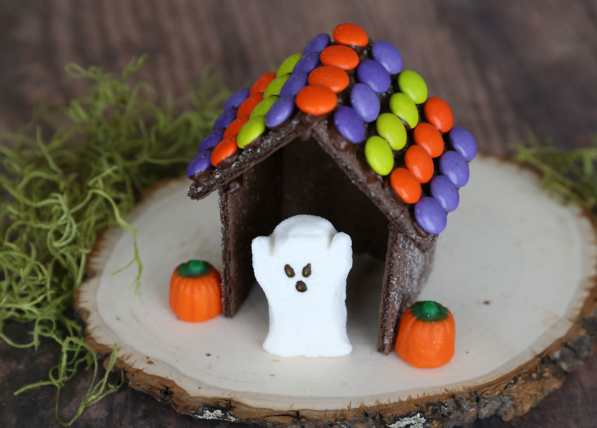 Halloween gingerbread house made from chocolate graham crackers with ghost peeps