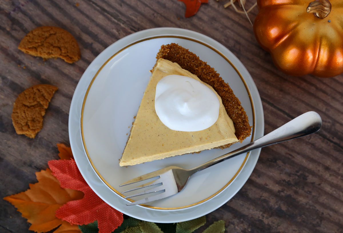 Slice of no bake pumpkin cheesecake on a white plate with whipped topping and a fork