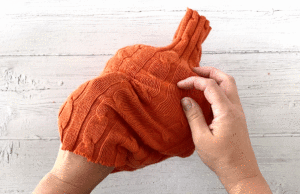 Hands placing a sweater sleeve over a roll of toilet paper to make a sweater pumpkin
