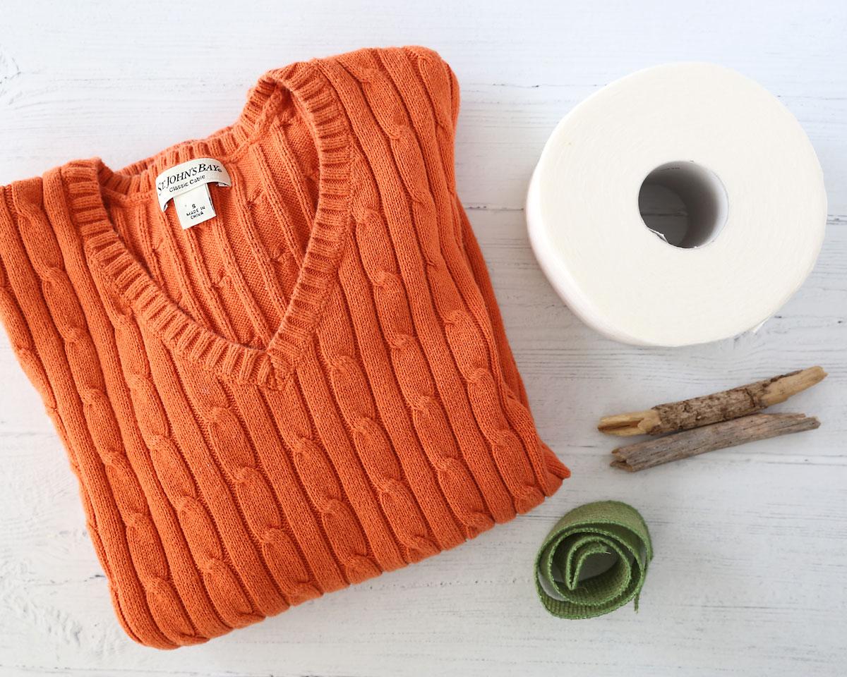 Supplies: Sweater, toilet paper, sticks, green ribbon