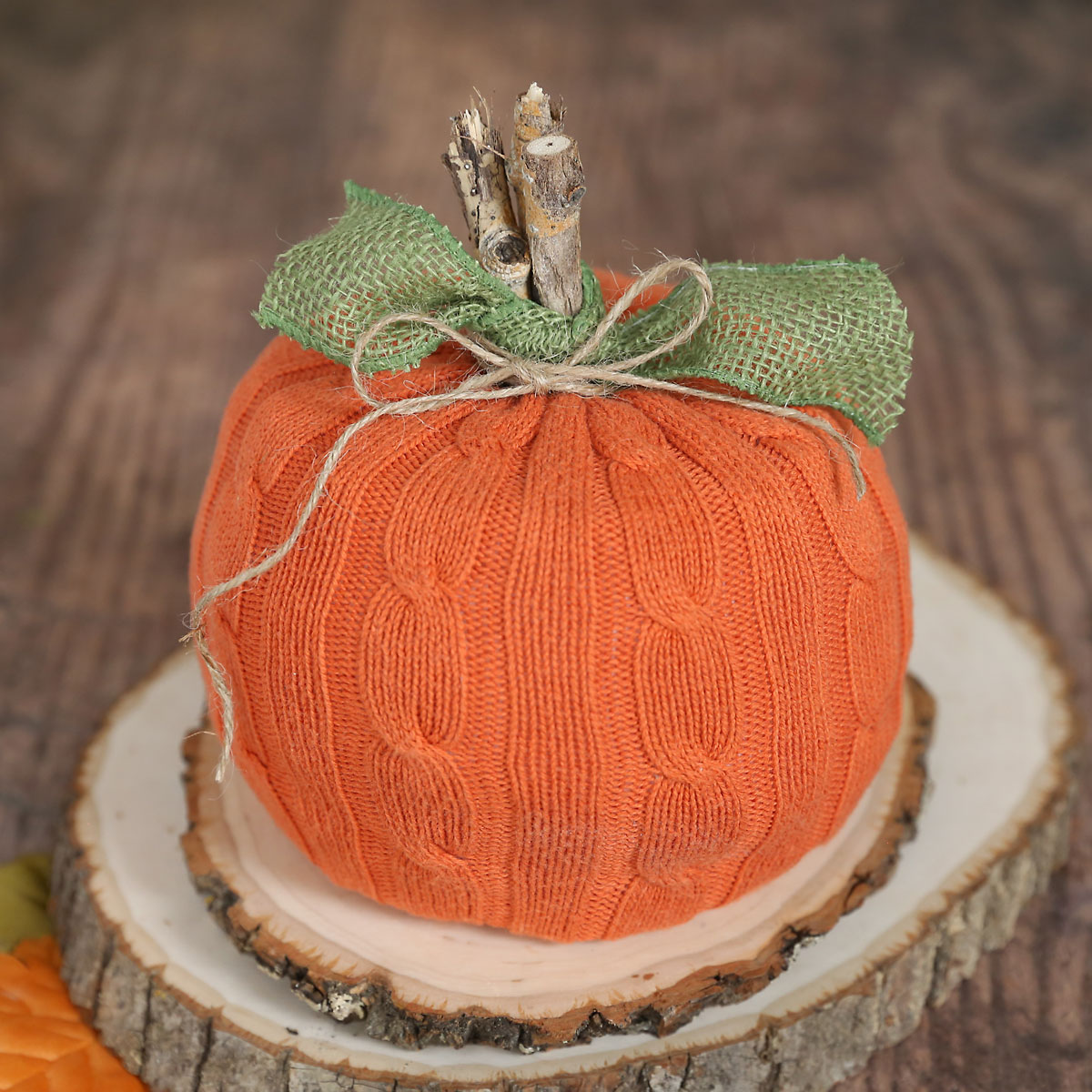 Pumpkin decoration made from a roll of toilet paper covered with orange sweater fabric