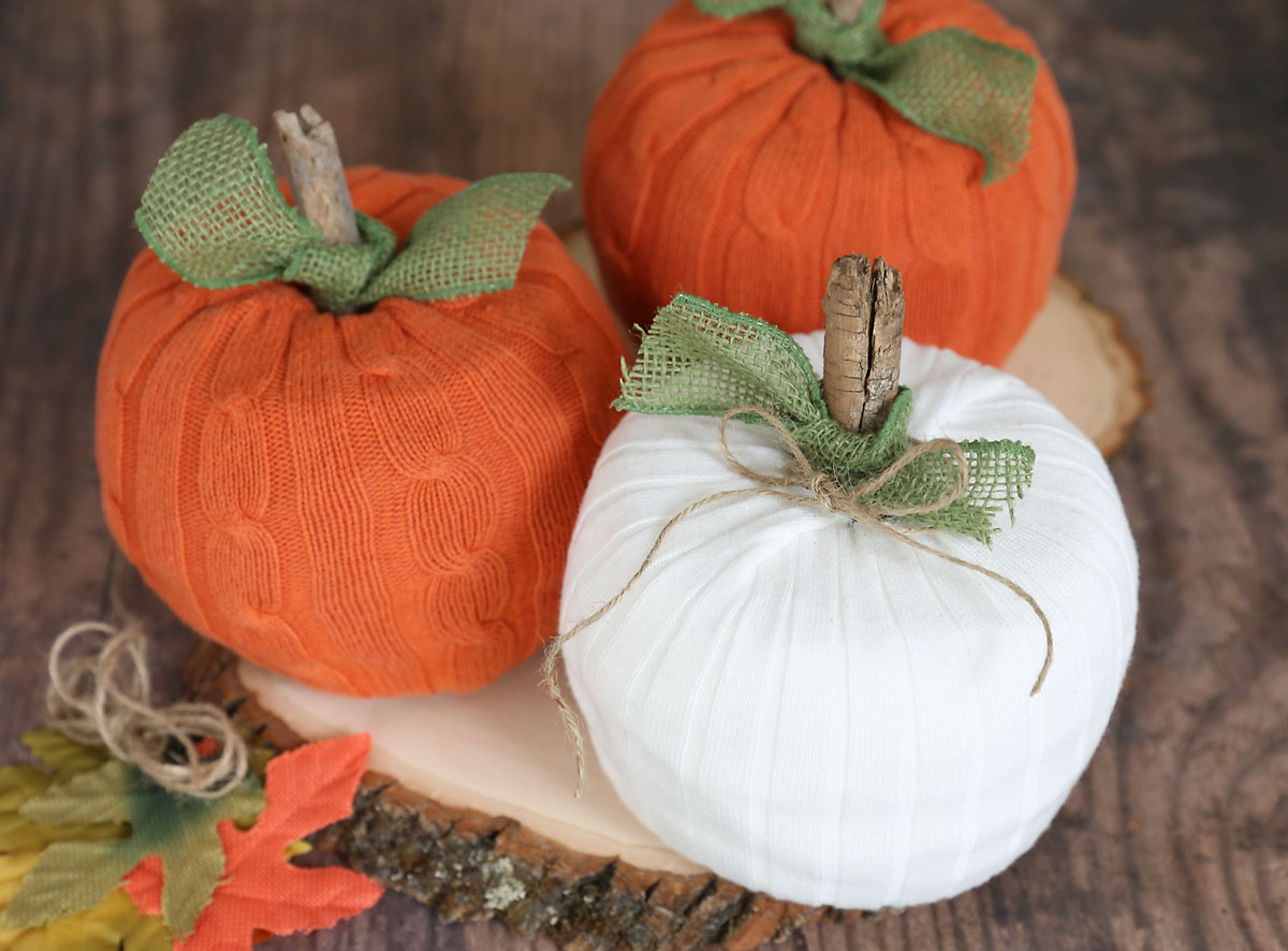 Toilet paper pumpkins made from an orange sweater and a white sweater