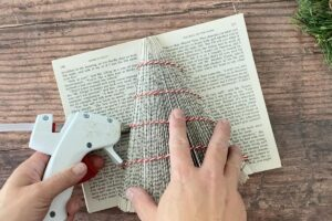 Folded book Christmas tree: hot glue gun attaching twine