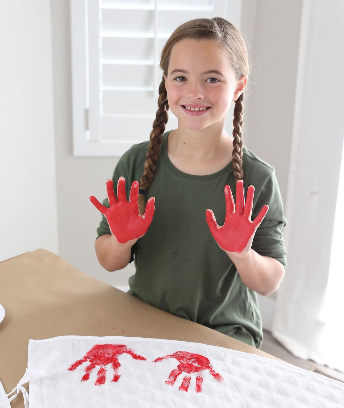 Girl making handprints on a Christmas tree skirt