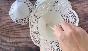 Slide largest doily cone down to hot glue