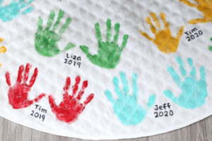 Cute handprint Christmas tree skirt with names and dates written by handprints