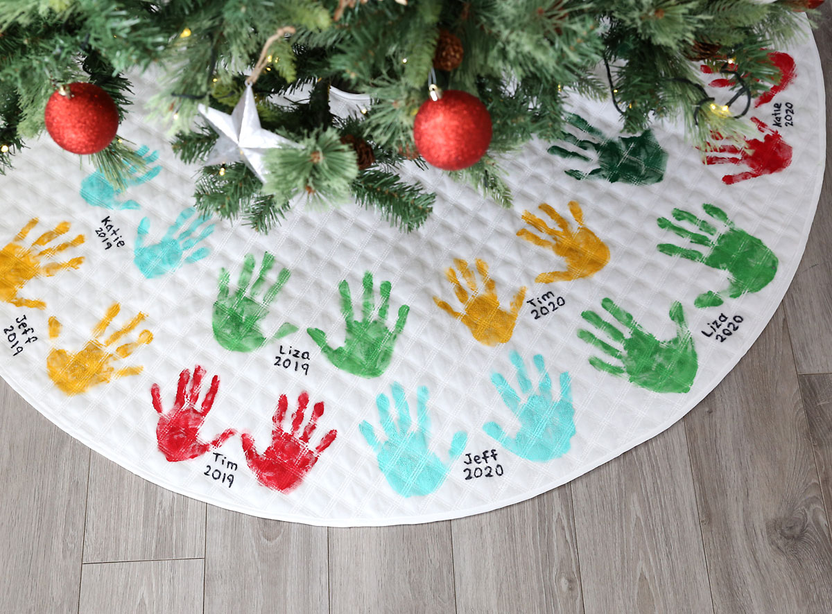 Christmas tree skirt decorated with handprints and names, lying under a Christmas tree