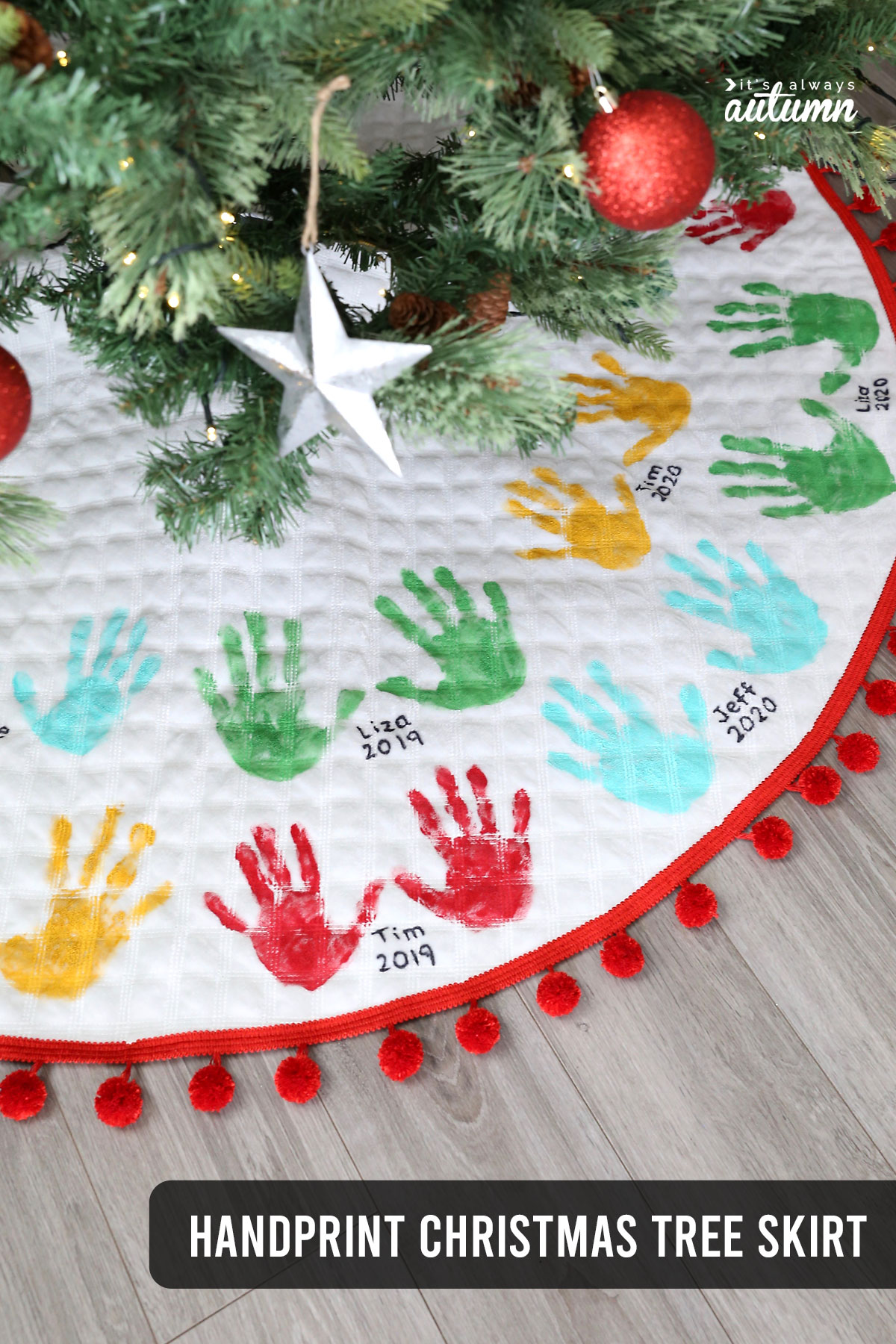 Christmas tree skirt decorated with handprints and names, trimmed with red pom poms