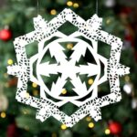 Snowflake cut from paper doily in front of a Christmas tree