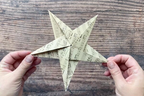 Hands holding paper origami star