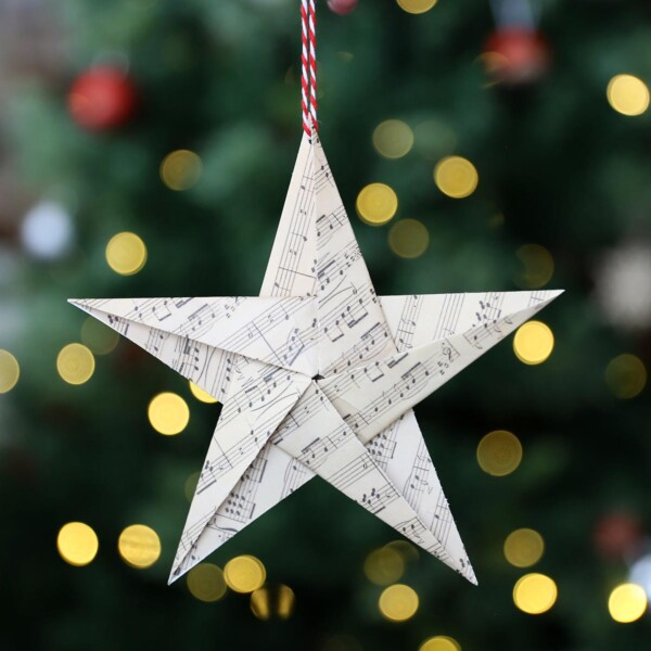 Paper origami star in front of a Christmas tree