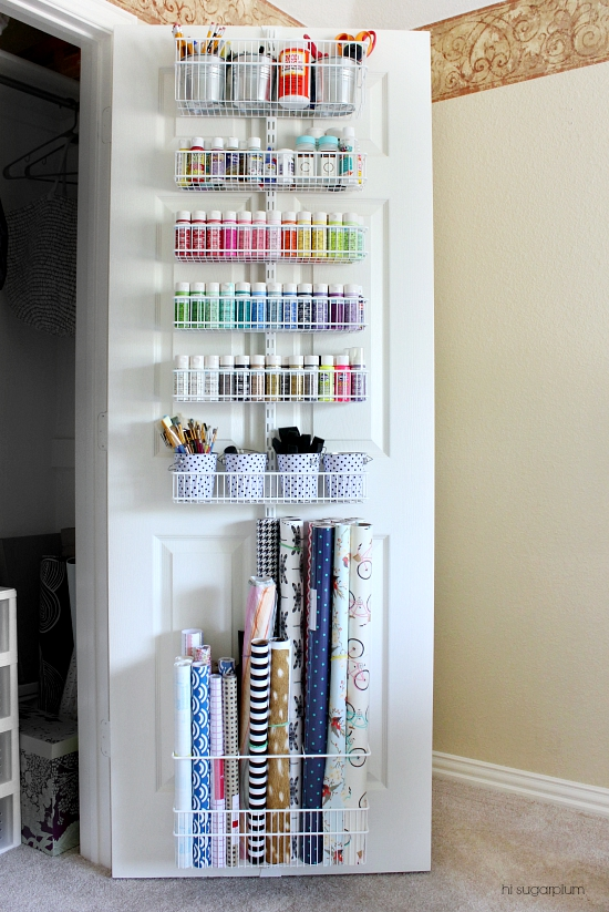Wire organizer hanging inside a closet door filled with craft supplies