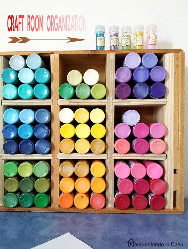 Acrylic paint bottles in various colors in DIY wood organizer crate