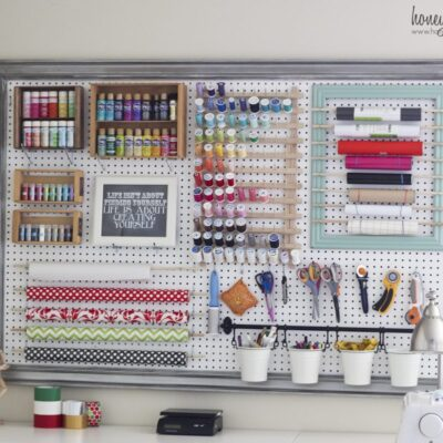Giant pegboard on a wall with craft supplies hanging from it