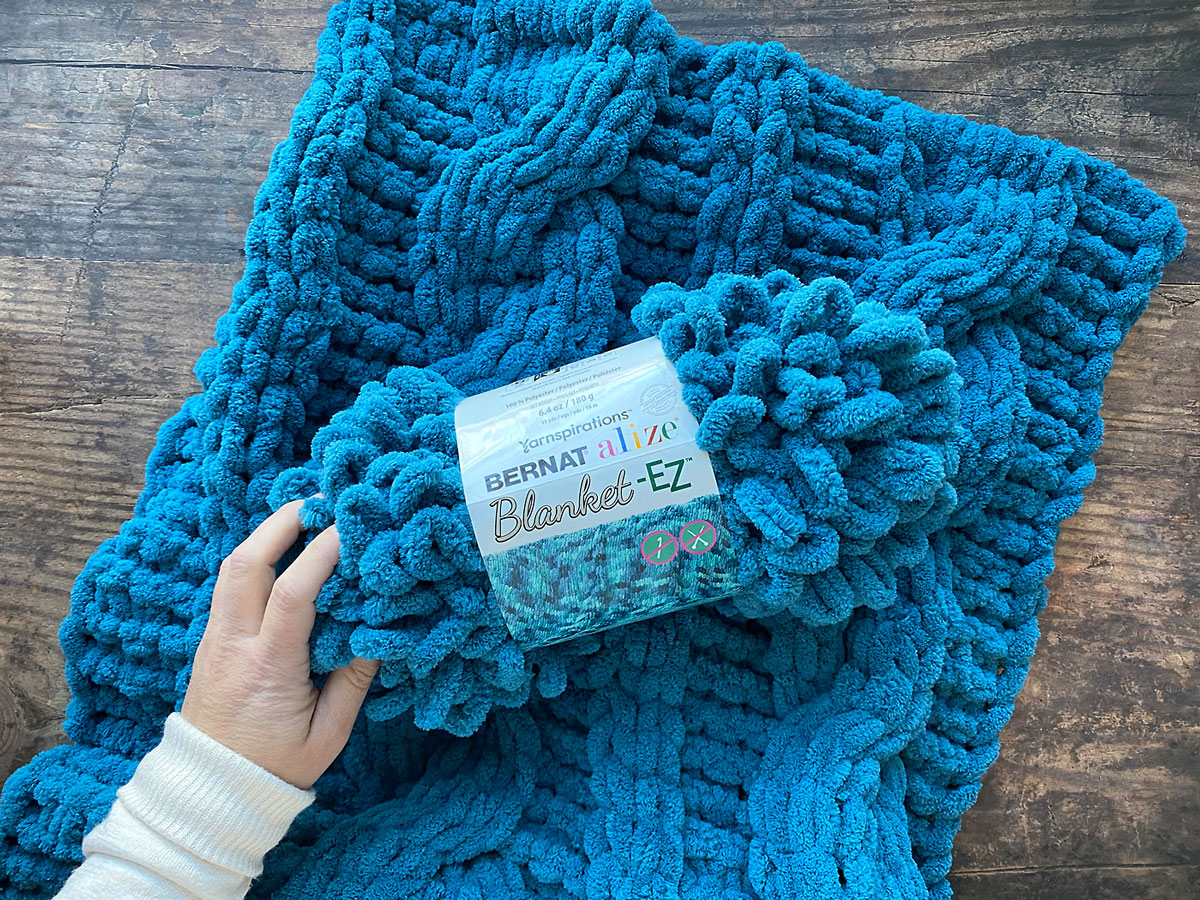 Ball of turquoise loop yarn and finger knit blanket.