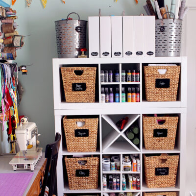 White cube storage unit with wicker baskets and craft supplies