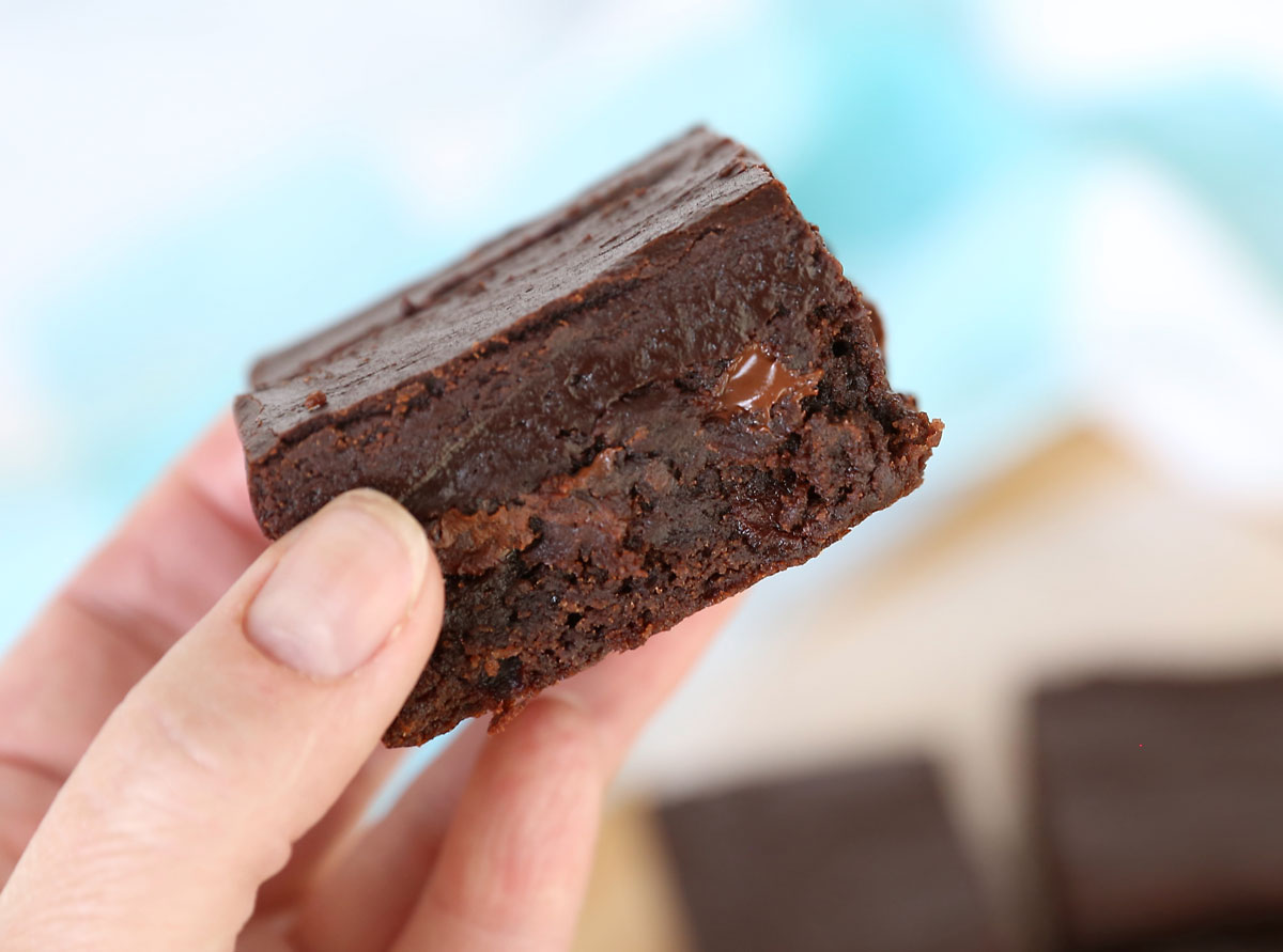 Hand holding a brownie with chocolate chips and fudge frosting