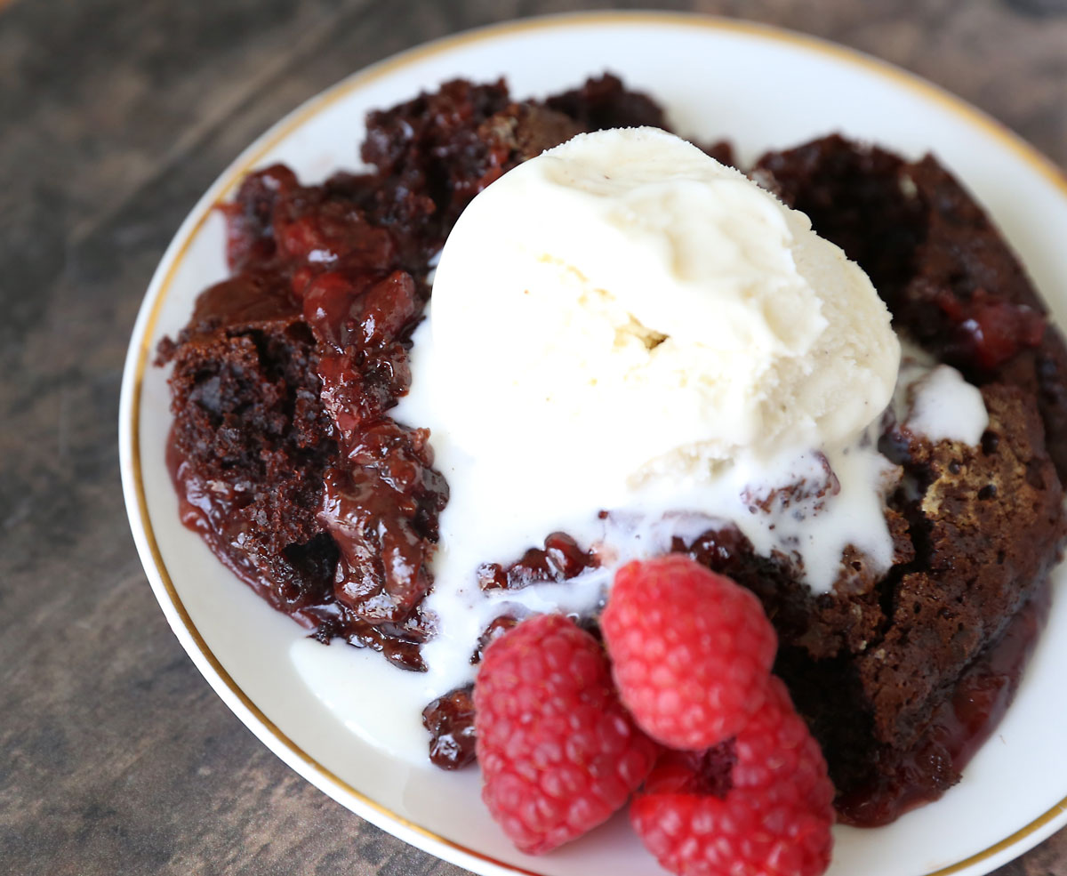 Chocolate raspberry cobbler on a plate with melting vanilla ice cream and raspberries