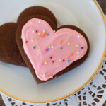 Heart shaped chocolate sugar cookie with pink frosting and sprinkles