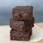 Stack of fudgy chocolate brownies on a cutting board