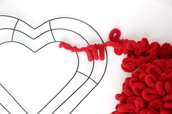 Red loop yarn with one end tied to a wire heart shaped wreath form