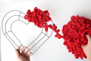 Hand holding a heart shaped wreath form wrapping red loop yarn around it