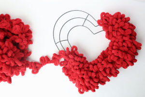 Red loop yarn covers most of the heart shaped wreath form