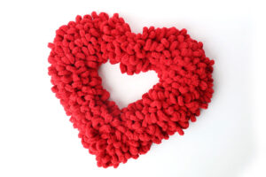 Heart shaped wreath covered in fluffy red loops of yarn