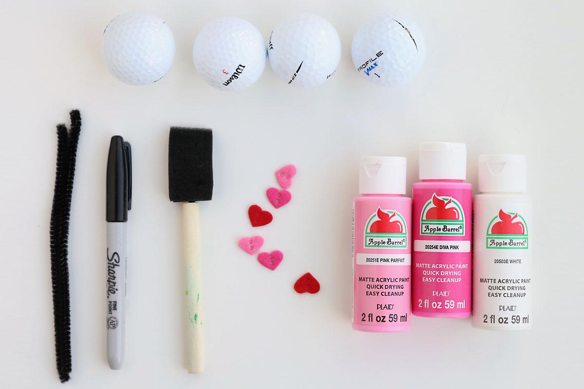 Love bug craft supplies: golf balls, acrylic paint, felt hearts, paint brush, sharpie marker, pipe cleaner