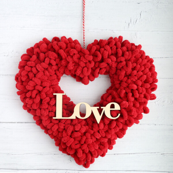Heart shaped wreath covered in red loop yarn with a wooden cutout of the word Love on it and hanging from twine