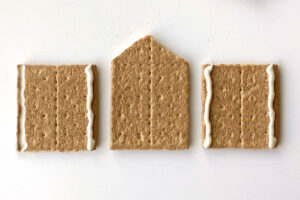 Roof support graham cracker in the center with a cracker half on either side; cracker halves both have melted white chocolate piped down either side