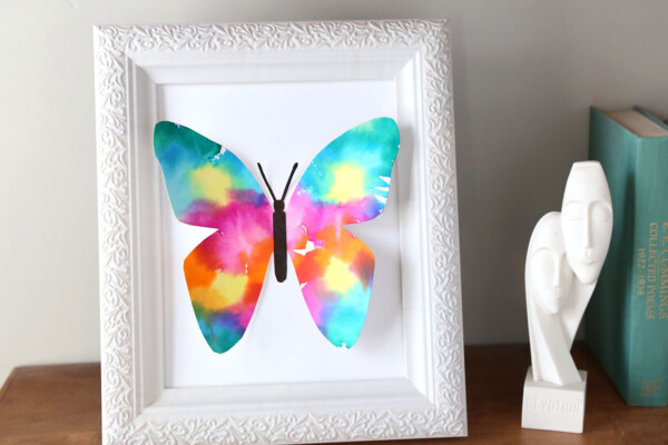 Colorful butterfly made of paper in a white picture frame on a shelf with a small white decorative figurine
