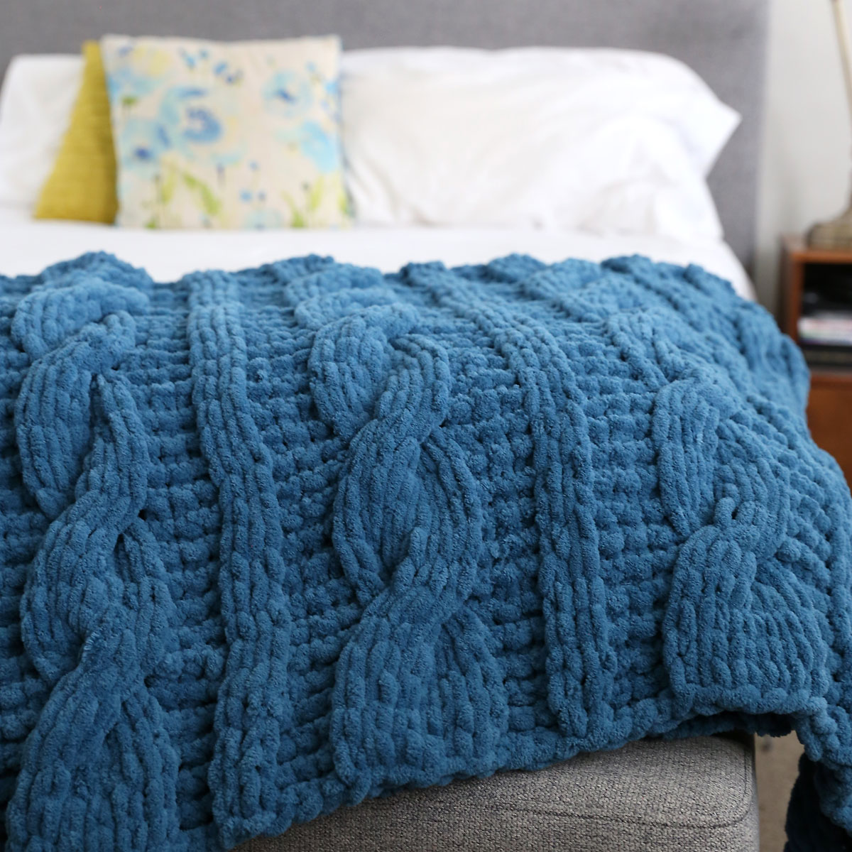 Blue handmade cable knit blanket on a bed