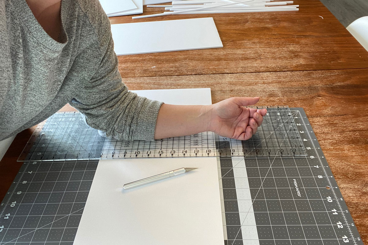 Cutting mat with foam core board on it, large ruler with person's forearm on the ruler to stabilize it in place; exacto knife